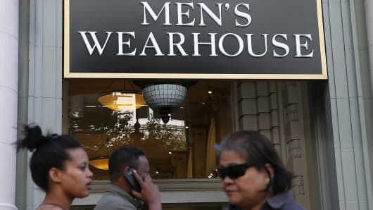 Pedestrians walk by a Men's Wearhouse retail store in San Francisco, California.