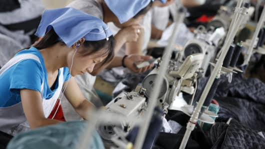 Picture taken on July 15, 2013 shows laborers producing clothes waiting to be exported to the EU in a factory in Huaibei, north China.