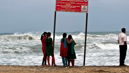 A group of Indian girls watch high tidal waves on the beach in Visakhapatnam on October 12, 2013.