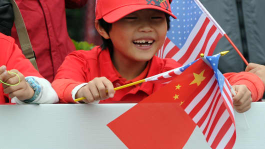 A Chinese boy waves a national flag together with a US flag.