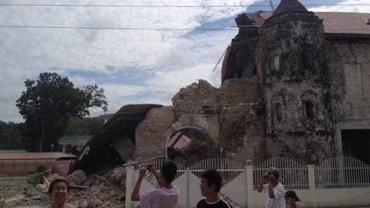 People walk past the damaged Church of San Pedro in the Philippine town of Loboc, Bohol after a major 7.1 magnitude earthquake struck the region on October 15, 2013.