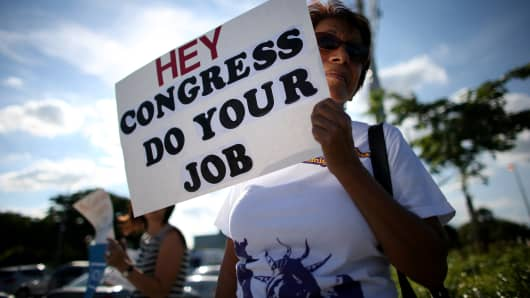 A woman holds a sign reading, 'Hey Congress Do Your Job' to protest against the partial government shutdown on October 15, 2013 in Doral, Florida. (File Photo).