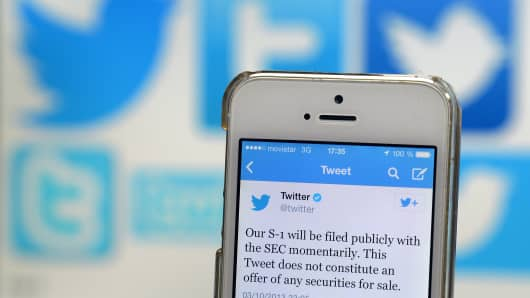 A Twitter tweet announcing the company's planned initial public offering (IPO) is pictured on a mobile telephone back-dropped by various twitter logos.