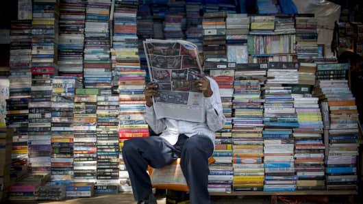 A book vendor reads a newspaper in Mumbai, India.