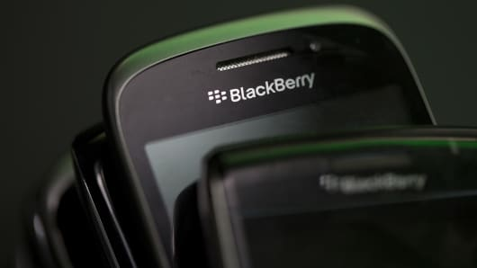 The BlackBerry logo sits on the screen of a BlackBerry smartphone.