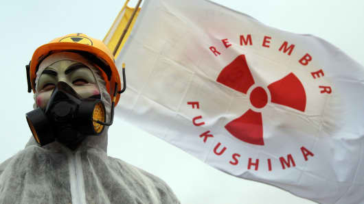 A masked protester stands in front of the gates to the Hinkley Point nuclear power station