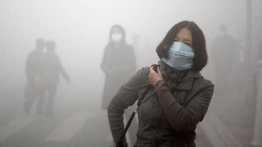 Pedestrians wearing masks walk along a road in Harbin, China.