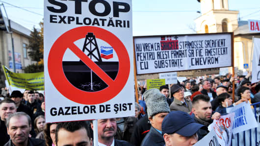 "A Romanian protester holds a banner reading in Romanian ""STOP shale gas exploits"" during a protest against the shale gas exploition in Barlad city, 250 kilometers northeast of Bucharest. (DANIEL MIHAILESCU/AFP/Getty Images)"