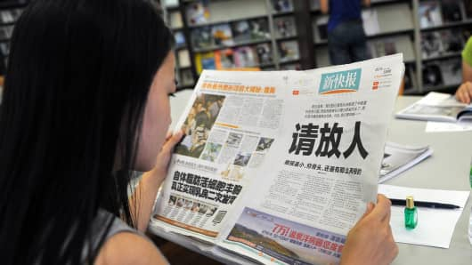 A woman reads the New Express newspaper that on October 23, 2013.