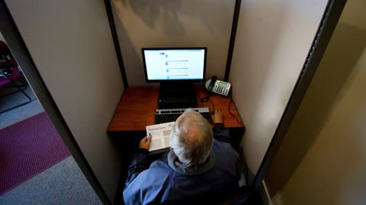 A customer looks over his health insurance options at a kiosk at the Montana Health Co-op in Helena, Mont.