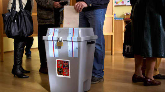 A voter casts ballot as others stand in line during the first day of the Czech early election on October 25, 2013 in Prague, Czech Republic.