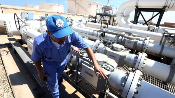 A file photo showing a Libyan oil worker from the Libyan National oil and gas company checks an oil pipelines at the Zawiya oil installation in Zawiya, Libya.