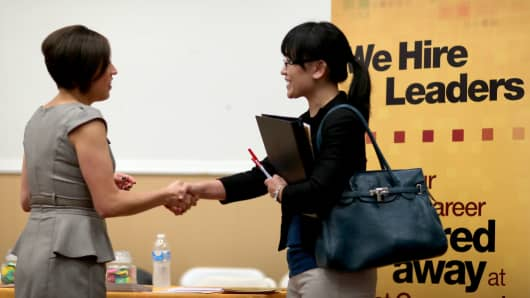Melinda Walker (R) shakes hands with Angelina Tennis, a recruiter at First Command Financial Services, during a job fair.