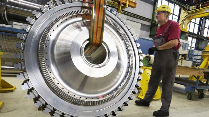 A worker assists in moving a disc of a gas turbine at the Siemens gas turbine plant in Berlin, Germany.