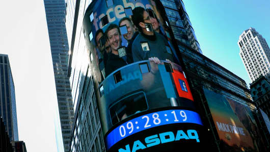 An image of Mark Zuckerberg, chief executive officer of Facebook Inc., left, with Robert Greifeld, chief executive officer of Nasdaq OMX Group, right, is projected at the Nasdaq MarketSite in New York, May 18, 2012.