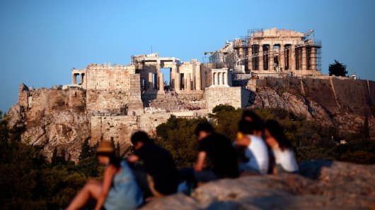 Tourists sit on rocks with a view of the Parthenon temple on Acropolis Hill in Athens, Greece