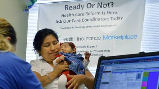 A woman holding her daughter receives information about the Health Care Reform, popularly known as Obamacare.