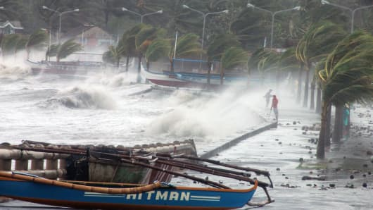 Residents stand along a sea wall as high waves pounded them amidst strong winds as Typhoon Haiyan hit the city of Legaspi, Albay province, south of Manila on November 8, 2013.