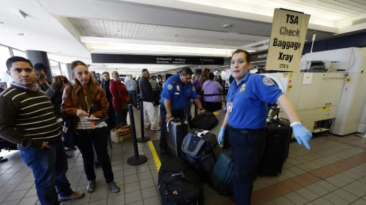 TSA workers screen luggage at LAX Terminal 2 a day after the fatal shooting.