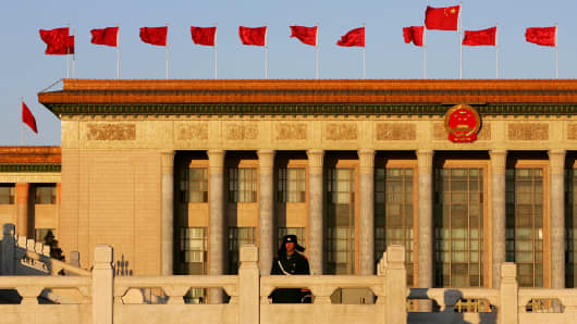 A Chinese policeman stands guard in front of the Great Hall of the People during sunrise.