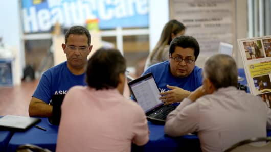 Insurance agents with Sunshine Life and Health Advisors help people with information about policies that are available to them under the Affordable Care Act at a kiosk setup at the Mall of Americas on November 5, 2013 in Miami, Florida.