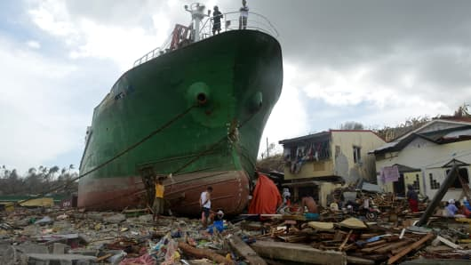 People walk among debris next to a ship washed ashore in the aftermath of Super Typhoon Haiyan in Tacloban, November 11, 2013.