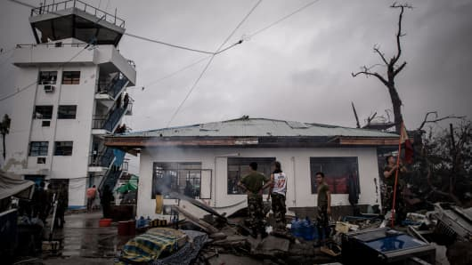 Military personnel stand by a building damaged by typhoon Haiyan at the airport in Tacloban, on the eastern island of Leyte on November 12, 2013