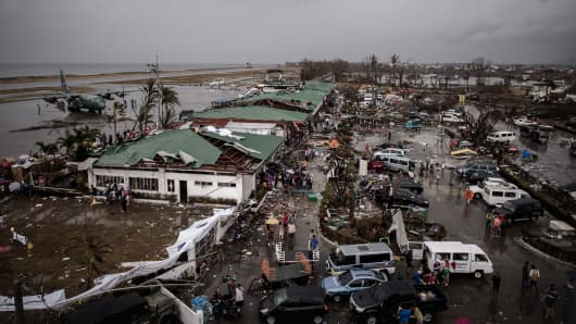 A general view from the damaged control tower of the airport shows a C-130 aircraft (L) taking part in evacuation operations in Tacloban.