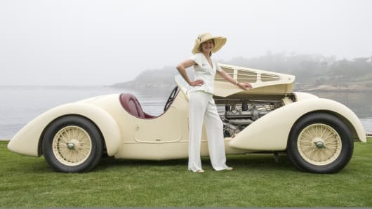 An attendee poses for a photograph in front of a 1934 Alfa 8C2300 Zagato Body during the 2013 Pebble Beach Concours d' Elegance in Pebble Beach, California.