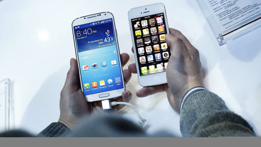 a Samsung Electronics Co. Galaxy S4 smartphone, left, next to an Apple Inc. iPhone 5.