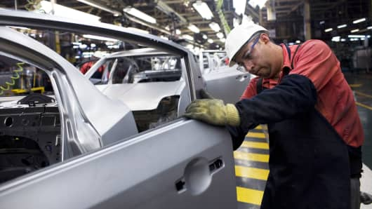 An employee carries puts the finishing touches on a car at the Nissan Motor Co. plant in Aguascalientes, Mexico.