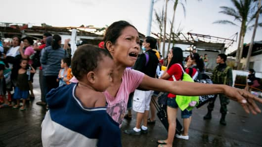 Survivors of Typhoon Haiyan wait to board a C-130 aircraft during the evacuation of hundreds of survivors from Tacloban, Philippines.