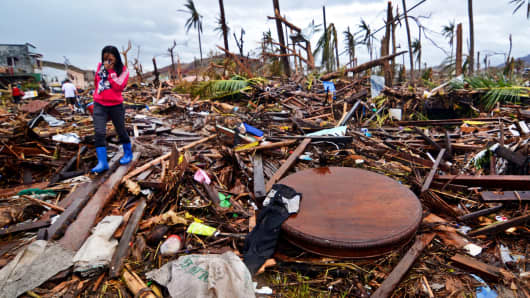 A woman navigates a road filled with debris in Leyte, Philippines, an area devastated by Typhoon Haiyan.