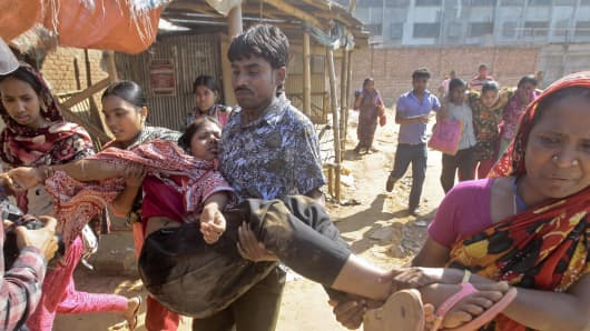 Bangladeshi garment workers assist their colleagues injured during clashes with police in Ashulia, outskirts of Dhaka, Bangladesh, Tuesday, Nov. 12, 2013. Thousands of garment workers demanding higher pay clashed with police in Bangladesh for a second day Tuesday, leaving dozens of people injured and at least 200 factories closed, police said.