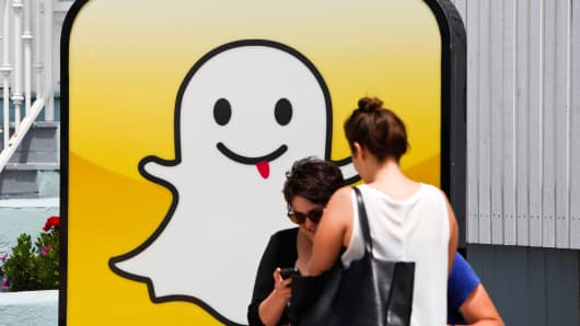 People take pictures in front of the Snapchat headquarters in Los Angeles.