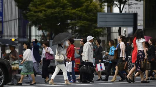 Pedestrians cross a street in the Ginza district of Tokyo.