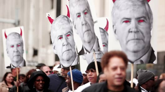 Protesters carry signs depicting Michigan Gov. Rick Snyder as a devil at a rally last month.