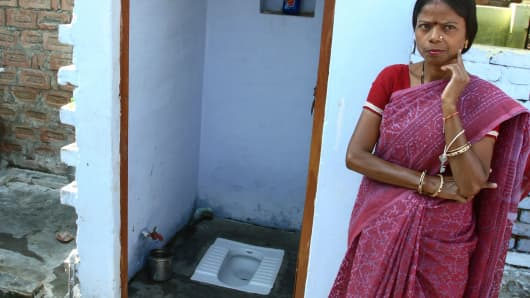 A woman stands next to her newly installed toilet in Agra, India.