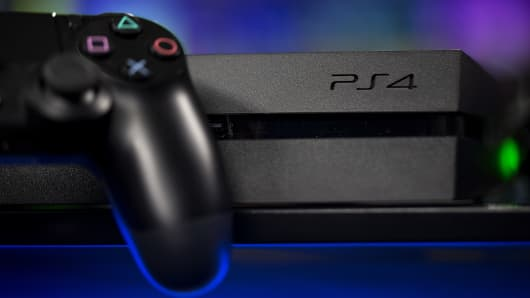 A Sony PlayStation 4 (PS4) controller sits next to the company's games console, manufactured by Sony Corp.