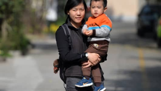 A mother carries her son on a street in Shanghai on November 16, 2013.