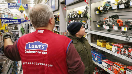 An employee helps a customer shop for a sander at a Lowe's home improvement store in Chicago, Illinois