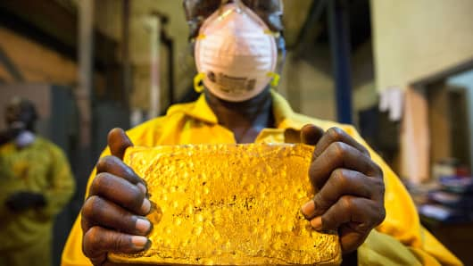 A mine worker displays a large ingot of gold during the refining process at the Loulo-Gounkoto gold mine complex operated by Randgold Resources Ltd. in Loulo, Mali, Nov. 1, 2013.