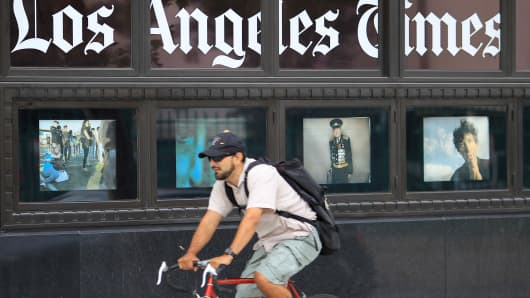 A bicyclist passes photos displayed on the Los Angeles Times building in Los Angeles.