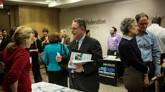 Job seekers speak to potential employers at a jobs fair for people 50-years-old and older on November 20, 2013 in New York City.