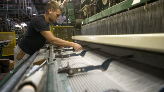 An employee adjusts an industrial-sized loom as it creates a roll of carpet at the Bloomsburg Carpet Industries Inc. manufacturing facility in Bloomsburg, Pennsylvania.