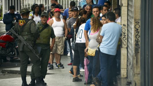 People line up outside an electrical appliances store in Caracas.