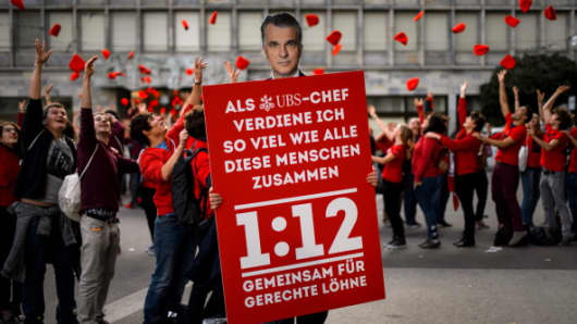 Holding a placard with the face of the CEO of Swiss banking giant UBS Sergio Ermotti, members of the youth organization JUSO of the Swiss Social Democrats (SP) take part on November 2, 2013 in the centre of Zurich in a demonstration in favour of their initative '1:12' to limit the amount of money companies pay their managers.