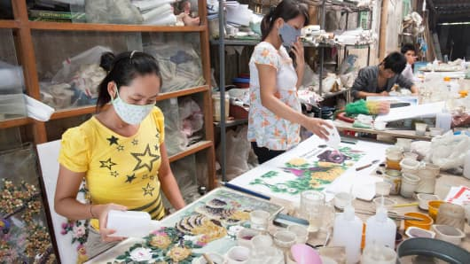 Workers at a shop selling paintings made from precious stone in Yen Bai, about 300 kms north of Hanoi.