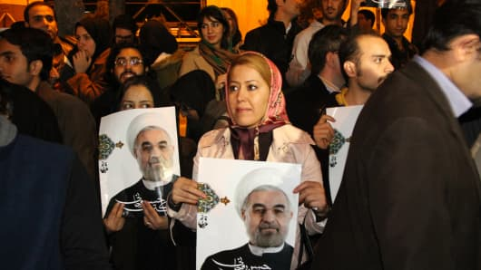 Iranians hold portraits of President Hassan Rouhani in Tehran on November 24, 2013.
