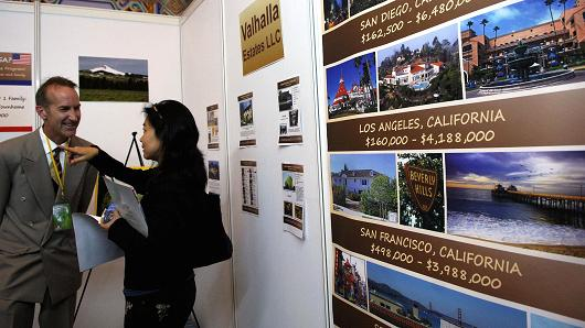 A salesperson introduces properties to a potential buyer at the Sino-U.S. Real Estate Exhibition Fair in Beijing.